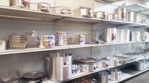 Steel sauce pans of various sizes on shelves inside showroom